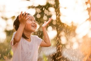 Happy asian little girl having fun to play with the rain